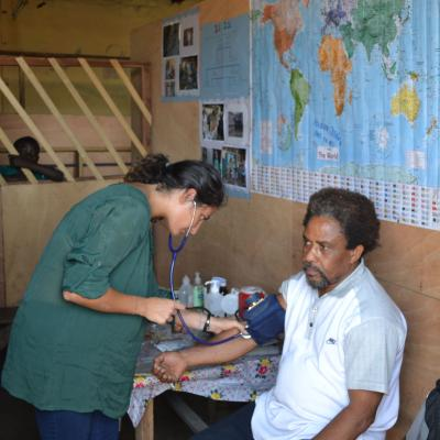 A Projects Abroad volunteer doing a basic checkup on man at her Spring Break Public Health placement in Ghana